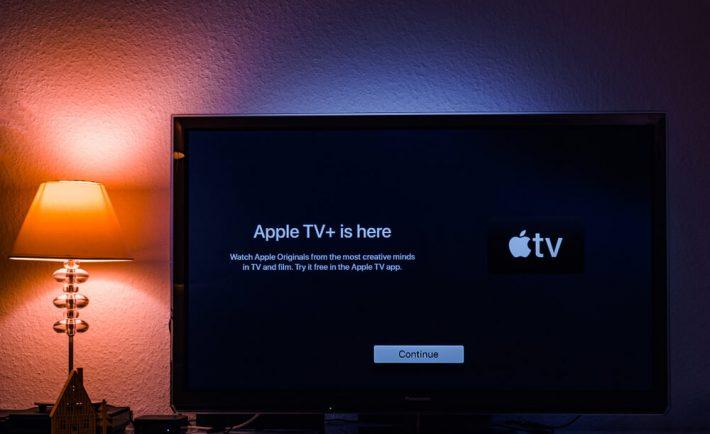 widok telewizora z włączonym Apple TV, na tle białej ściany z kolorowym oświetleniem