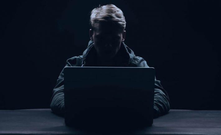 postać hakera siedzącego za laptopem. Ciemne kolory.