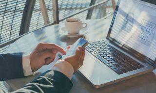 Człowiek wpisujący kod z telefonu, aby zalogować się gdzieś, za pomocą komputera.